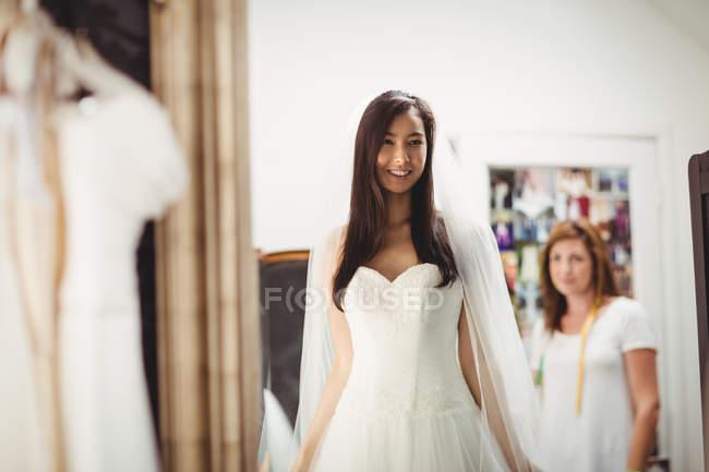 Усміхається жінка приміряє Весільне плаття в магазин — стокове фото