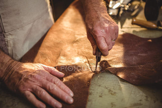 Hands of shoemaker cutting a piece of leather in workshop — Stock Photo