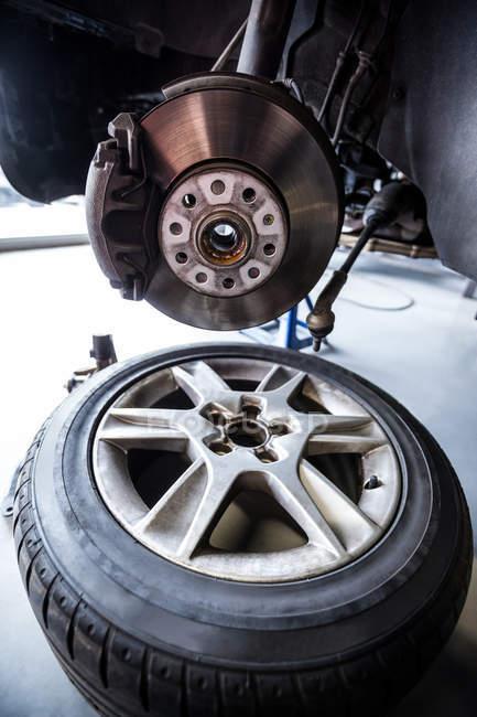 Primer plano de rueda de rotura y piezas de repuesto en el garage de la reparación - foto de stock