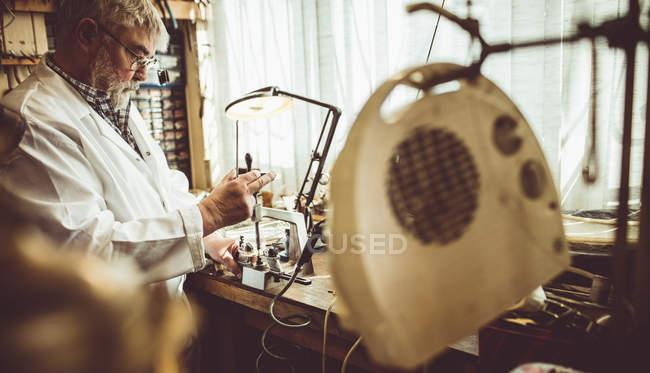 Horloger à l'aide d'une fraiseuse d'horlogerie à l'atelier — Photo de stock