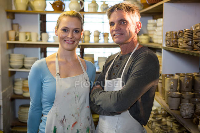 Portrait of happy potters standing in pottery workshop — Stock Photo