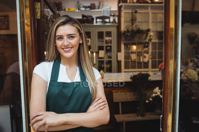 Portrait of female florist with arms crossed at her flower shop — Stock Photo