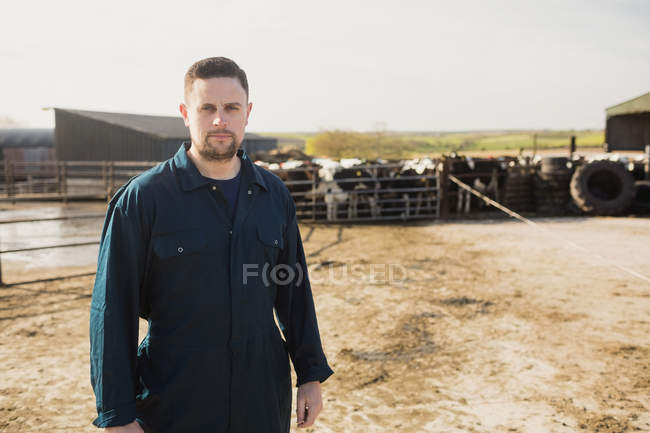 Portrait du travailleur agricole jeunes debout sur le terrain contre le ciel — Photo de stock