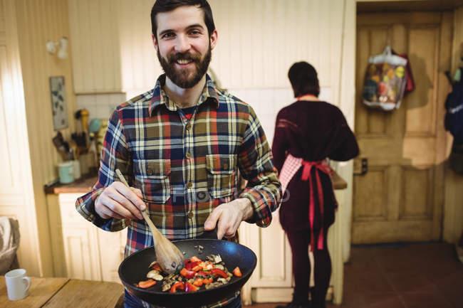 Homem preparando comida na cozinha em casa com a mulher em segundo plano — Fotografia de Stock