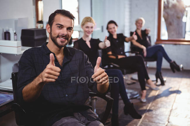 Portrait of smiling hairdressers showing thumbs up in salon — Stock Photo