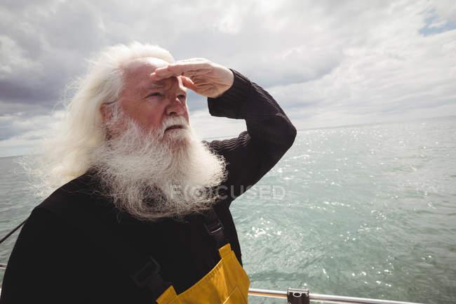 Fischer steht auf Fischerboot und schaut weg — Stockfoto