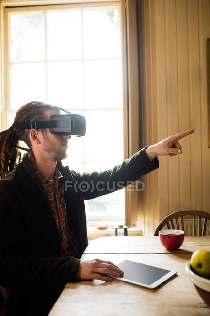 Hipster pointing while wearing virtual reality simulator at home — Stock Photo