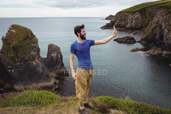 Человек делает селфи с мобильного телефона на скале — стоковое фото
