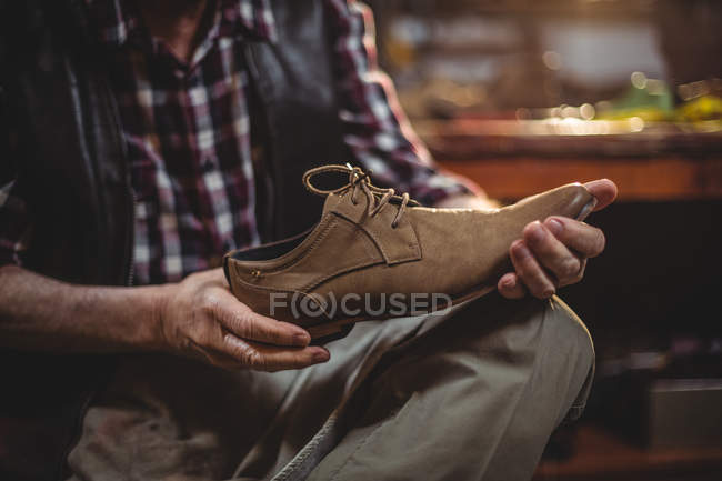 Mid section of shoemaker examining a shoe in workshop — Stock Photo