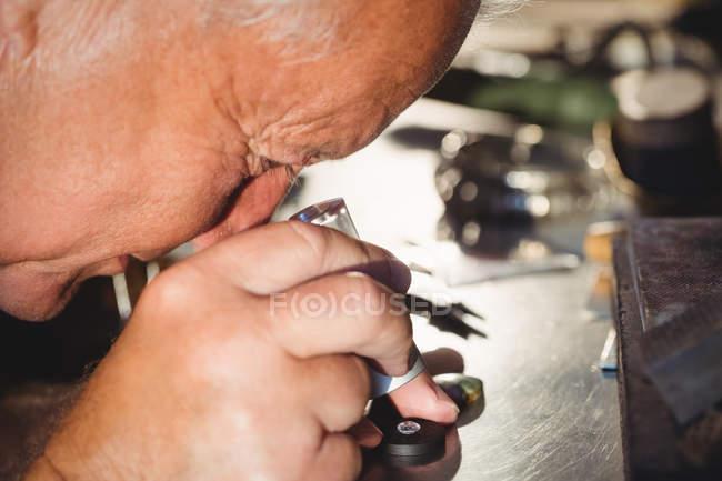Крупный план ювелира, осматривающего алмаз через лупу в мастерской — стоковое фото