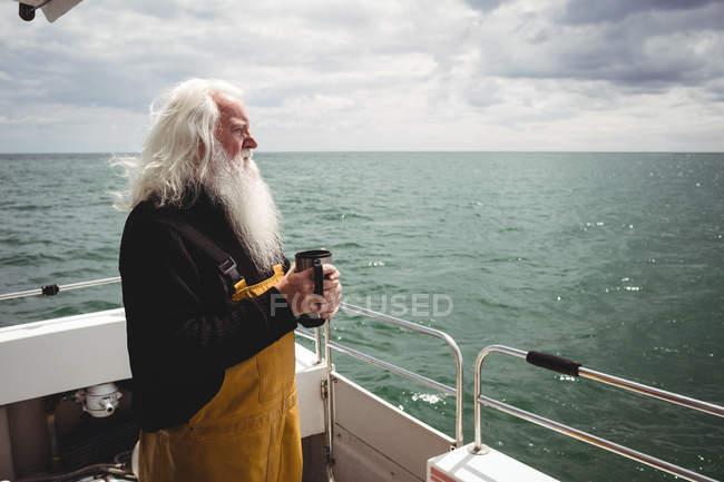 Nachdenklicher Fischer, der mit einer Tasse Kaffee auf dem Boot steht — Stockfoto