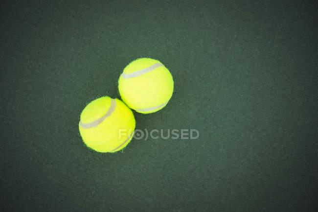 Primer plano de dos pelotas de tenis en corte verde - foto de stock