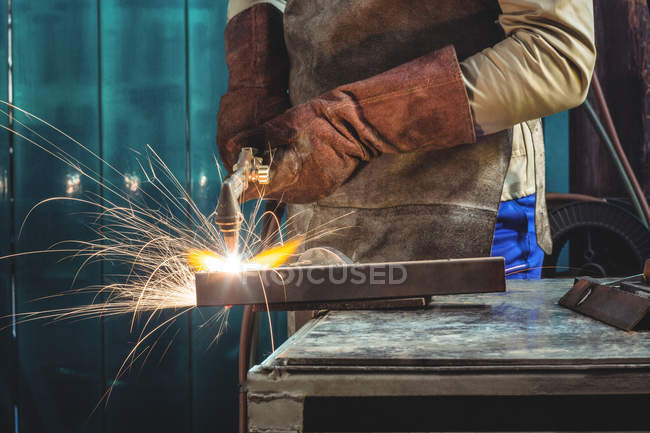 Cropped image of Male welder working on piece of metal in workshop — Stock Photo
