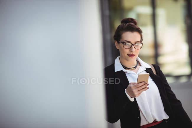 Giovane donna d'affari che tiene il telefono cellulare mentre si appoggia al muro — Foto stock