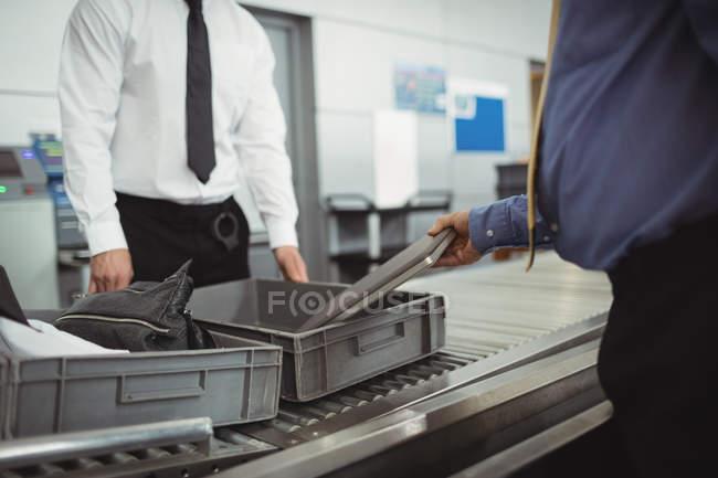 Hombre poner portátil en la bandeja para control de seguridad en el aeropuerto - foto de stock