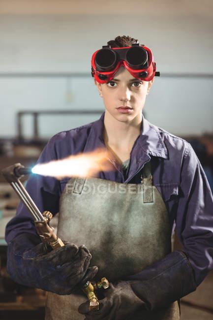 Soudeur femelle tenant la torche de soudage en atelier — Photo de stock