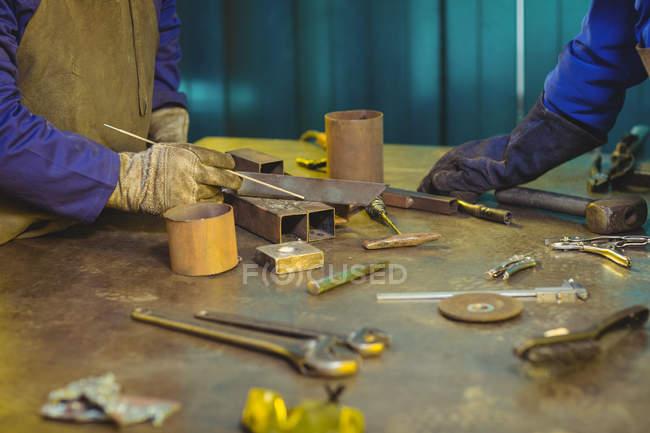Кадроване зображення чоловічих і жіночих зварювальники, які працюють разом в майстерні — стокове фото