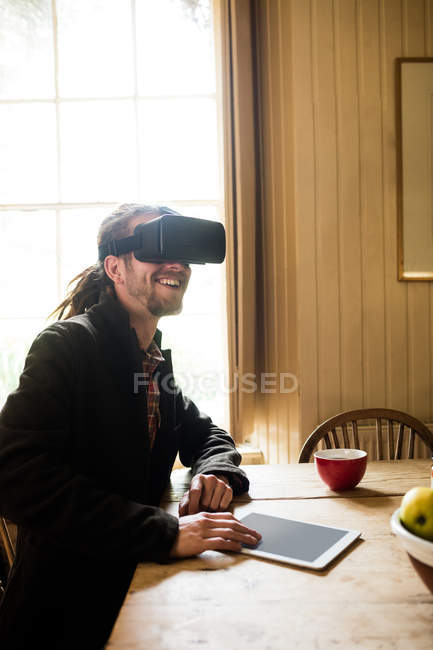 Smiling hipster wearing virtual reality simulator with digital tablet on table at home — Stock Photo