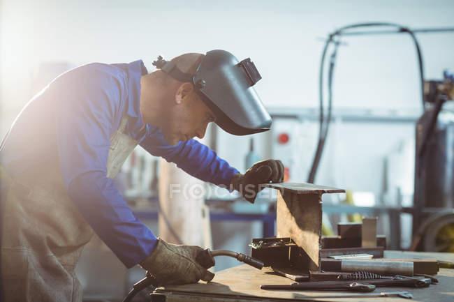 Male welder examining piece of metal in workshop — Stock Photo