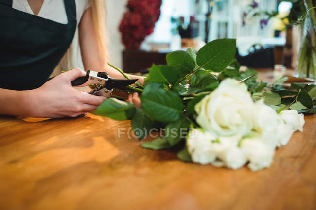 Cropped image of female florist trimming flower stems at her flower shop — Stock Photo