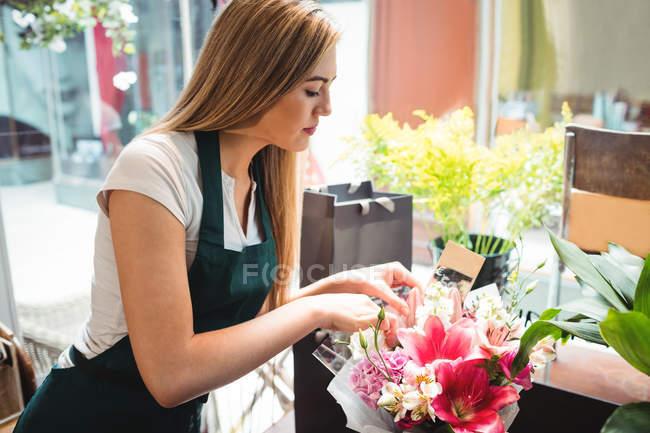 Femmina fiorista organizzare mazzo di fiori nel negozio di fiori — Foto stock