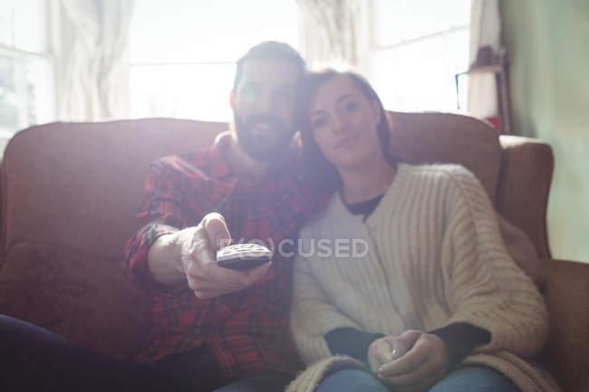 Coppia seduta sul divano con telecomando mentre guarda la televisione in soggiorno a casa — Foto stock
