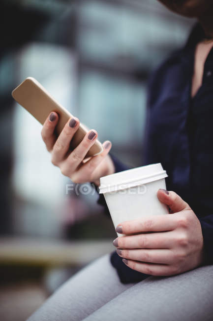 Midsection of businesswoman holding cellphone and disposable coffee cup — Stock Photo