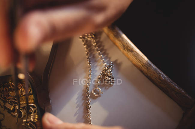 Cropped image of goldsmith preparing chain in workshop — Stock Photo