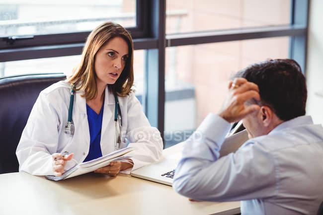 Medico alla scrivania che parla con il paziente in ospedale — Foto stock
