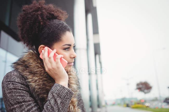 Умная женщина разговаривает по телефону снаружи здания — стоковое фото