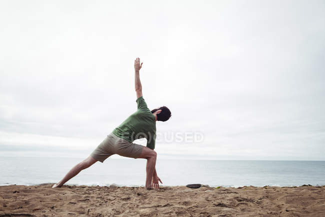 Rear view of man performing stretching exercise on beach — Stock Photo