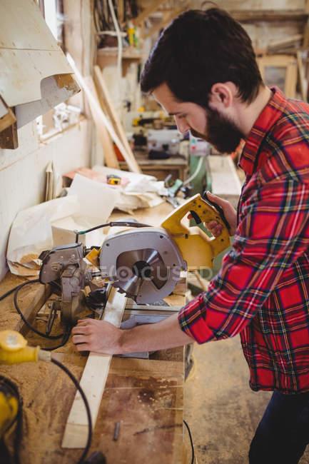 Людина різання дерев'яна Планка з Електропилки у верфі — стокове фото