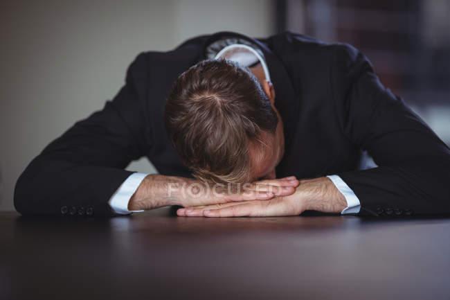 Homem de negócios exausto, sentado com a cabeça na mesa de escritório — Fotografia de Stock