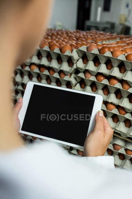 Personale femminile che utilizza tablet digitale in fabbrica di uova — Foto stock