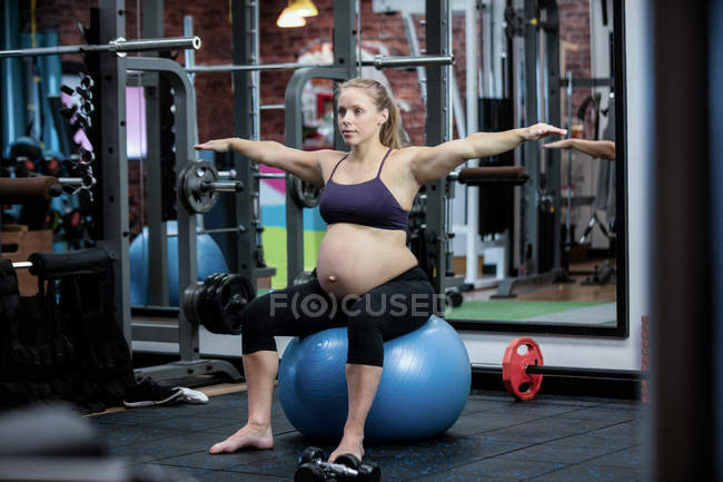 Pregnant woman preforming stretching exercise on fitness ball in gym — Stock Photo