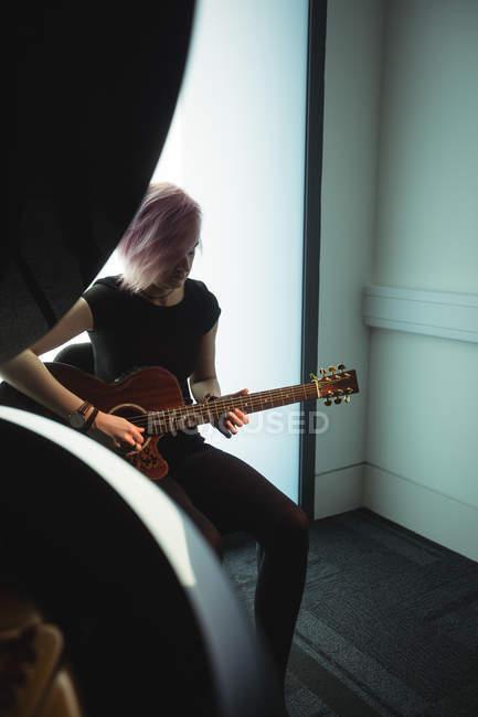 Frau spielt Gitarre in Musikschule — Stockfoto