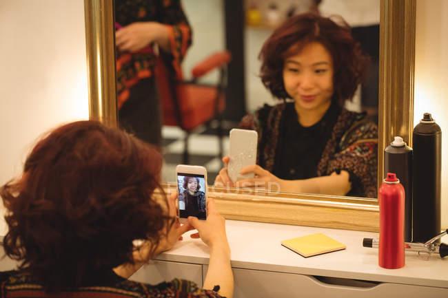 Stylish woman taking mirror selfie at hair salon — Stock Photo