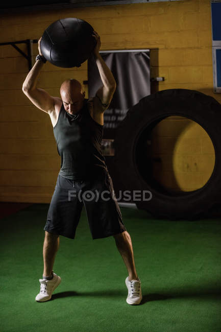 Handsome sportsman lifting weight in gym — Stock Photo