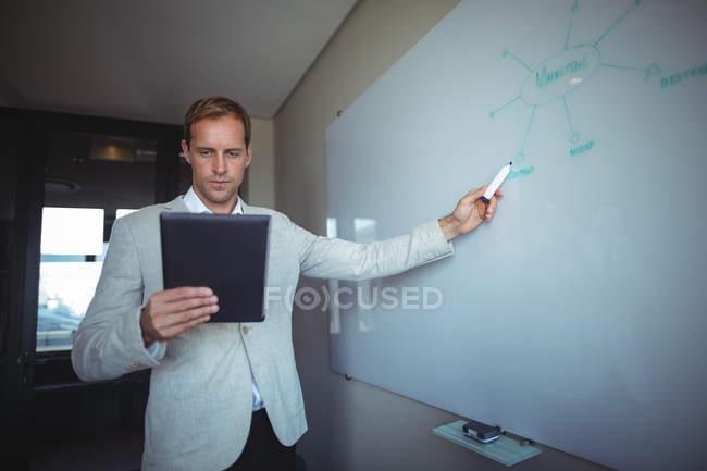 Geschäftsmann schaut auf digitales Tablet, während er im Büro auf Whiteboard schreibt — Stockfoto