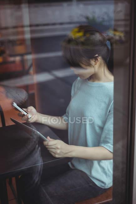 Молода жінка, використовуючи мобільний телефон і цифровий планшетний в кафе — стокове фото