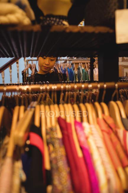 Jeune femme en choisissant des vêtements sur cintres au magasin de vêtements — Photo de stock