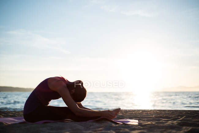 Side view of Woman performing yoga on beach on sunny day — Stock Photo