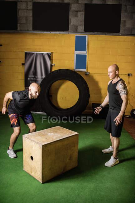 Два спортсмена работают над деревянной коробкой в фитнес-студии — стоковое фото
