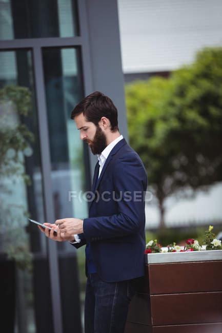 Uomo d'affari utilizzando il telefono cellulare al di fuori dell'ufficio — Foto stock
