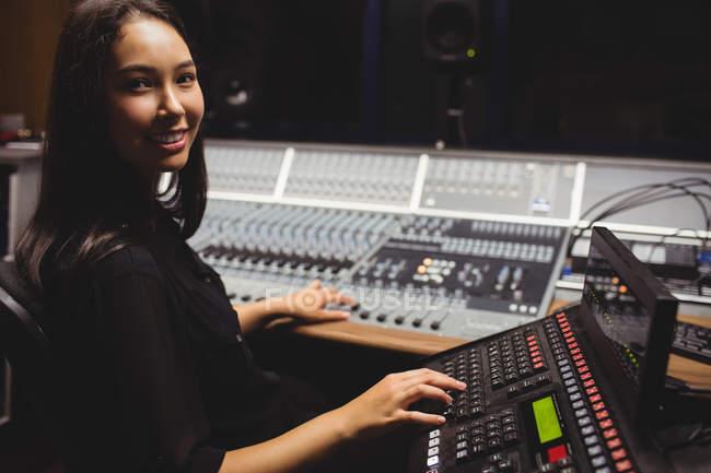 Estudante feminina usando teclado mixer som em um estúdio — Fotografia de Stock