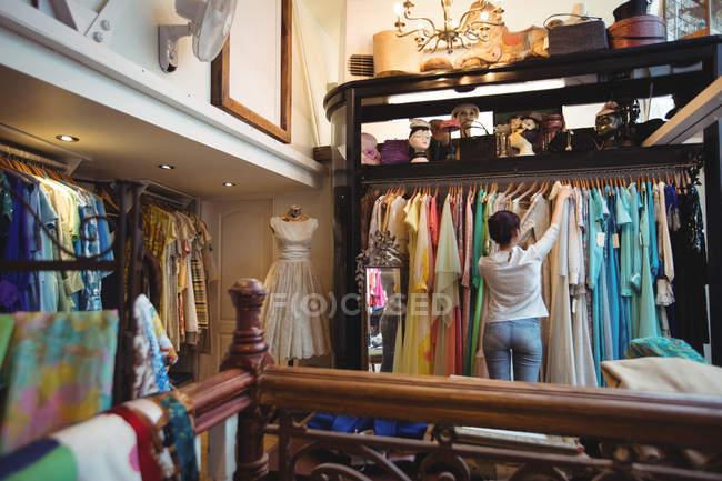 Femme de choisir un vêtements de cintres au magasin — Photo de stock
