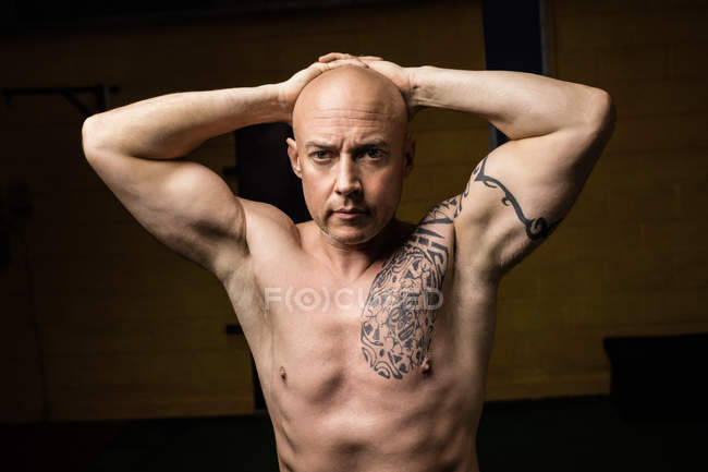 Portrait of tattooed shirtless thai boxer posing in gym — Stock Photo