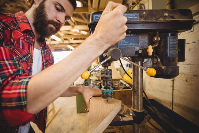 Человек сверлит яму на деревянной доске в лодочной мастерской — стоковое фото