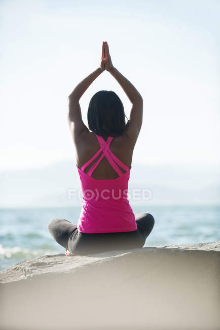 Rear view of woman performing yoga on rock on sunny day — Stock Photo