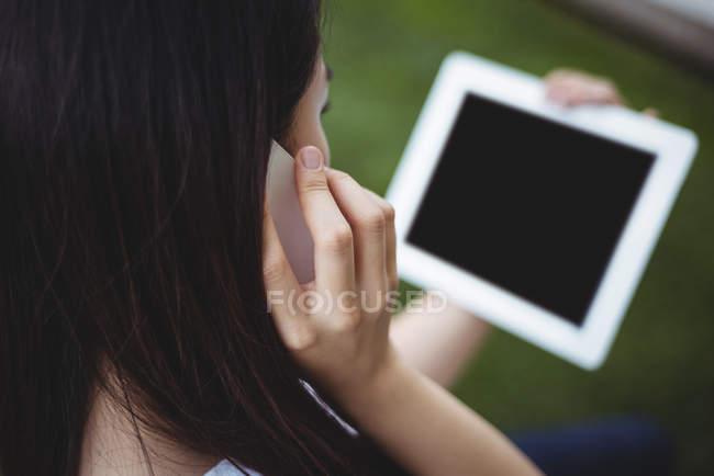 Крупным планом женщины говорят на мобильном телефоне при использовании цифрового планшета — стоковое фото